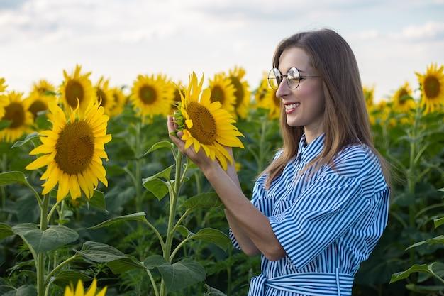 ひまわり畑で花を楽しむドレスとメガネの若い女性。 Premium写真