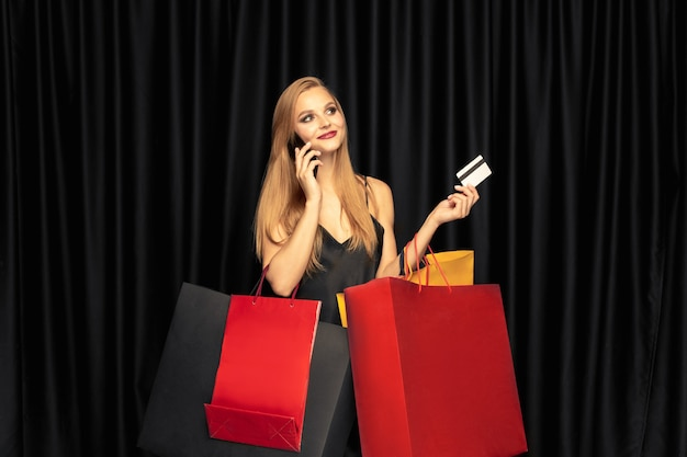 Молодая женщина в платье, делающем покупки на черной стене Бесплатные Фотографии