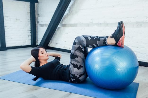 Молодая женщина в фитнес-одежде работая с голубым фитнес-мячом, изолированным на белой комнате. образ жизни! концепция фитнеса! Premium Фотографии
