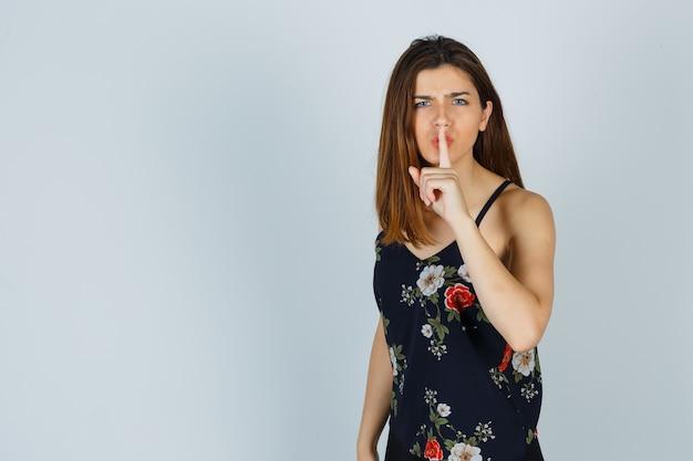 沈黙のジェスチャーを示し、暗いように見える花のトップの若い女性 無料写真