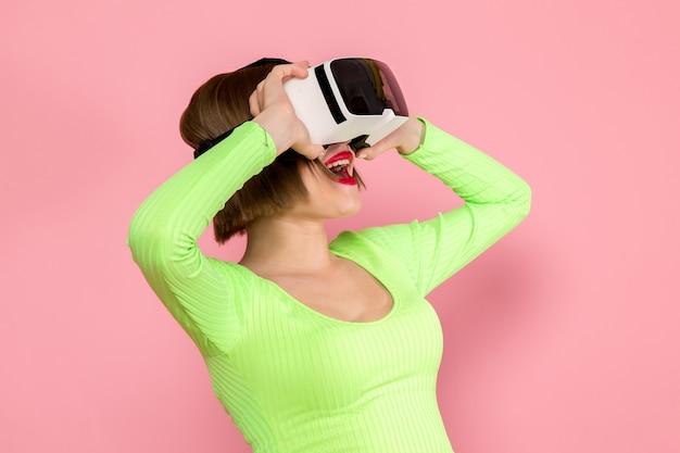 緑のシャツと灰色のスカートの仮想現実のゲームをプレイしようとして若い女性 無料写真