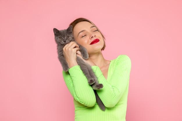 緑のシャツとかわいい灰色の子猫を保持している灰色のズボンの若い女性 無料写真
