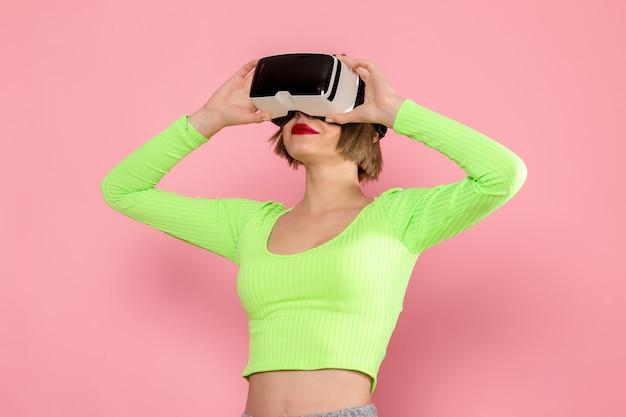 緑のシャツと灰色のズボンの仮想現実ゲームを試して若い女性 無料写真