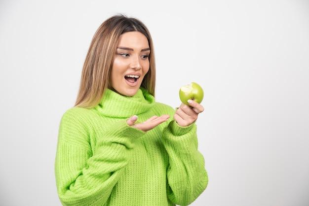 사과 들고 녹색 티셔츠에 젊은 여자 무료 사진