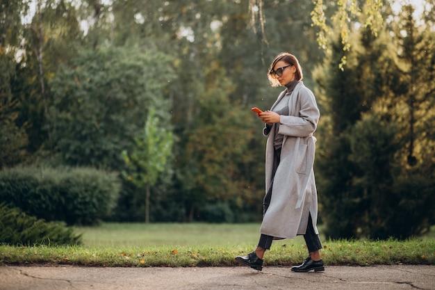 公園で電話で話している灰色のコートの若い女性 無料写真