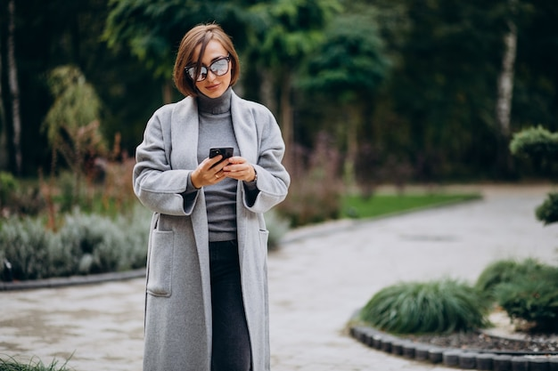 公園を歩く灰色のコートを着た若い女性 無料写真