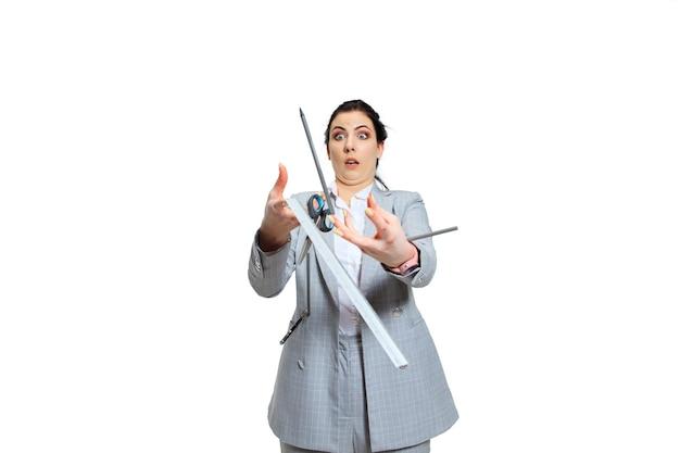 Молодая женщина в сером костюме теряет концентрацию. все идет не так, падает из рук, она пытается это поймать. понятие проблем офисного работника, бизнеса, проблем и стресса. Бесплатные Фотографии