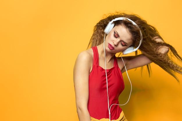 Молодая женщина в наушниках, веселье и смех, купальник вечеринка, желтое пространство Premium Фотографии