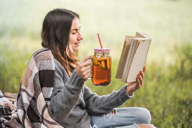 本を読んで手に飲み物を持って自然の中で若い女性 無料写真