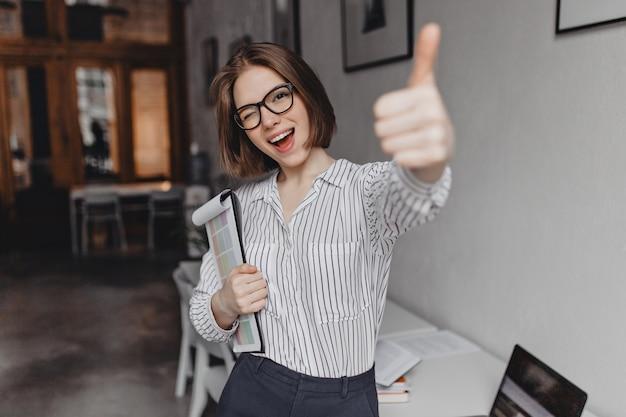 オフィススタイルの服と眼鏡の若い女性は、ドキュメント、ウィンク、親指を立ててタブレットを保持します。 無料写真