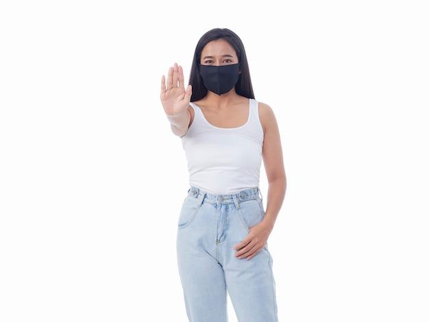 白い壁に停止ジェスチャーを示す保護マスクの若い女性 Premium写真