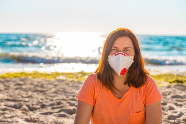 防護マスクの若い女性は海の近くのビーチに座っています。 Premium写真