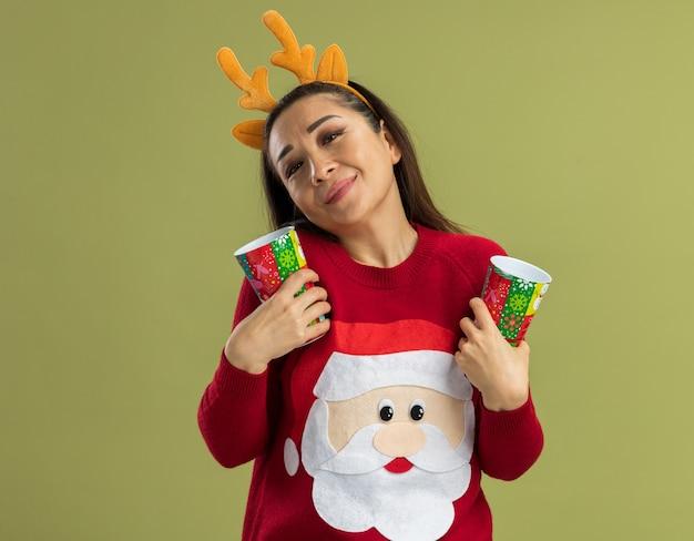 웃는 느낌 긍정적 인 감정을 찾고 다채로운 종이 컵을 들고 사슴 뿔과 함께 재미있는 테두리를 입고 빨간 크리스마스 스웨터에 젊은 여자 무료 사진