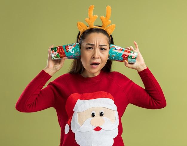녹색 배경 위에 서 혼란 스 러 워 찾고 그녀의 귀에 다채로운 종이 컵을 들고 사슴 뿔 재미 테두리를 입고 빨간 크리스마스 스웨터에 젊은 여자 무료 사진