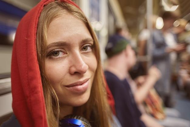 출퇴근 시간에 지하철에서 열차의 차에 승객의 배경에 빨간 까마귀에 젊은 여자. 프리미엄 사진