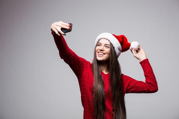 サンタの帽子をかぶった若い女性は灰色の壁に隔離の電話で自分撮りを取ります 無料写真
