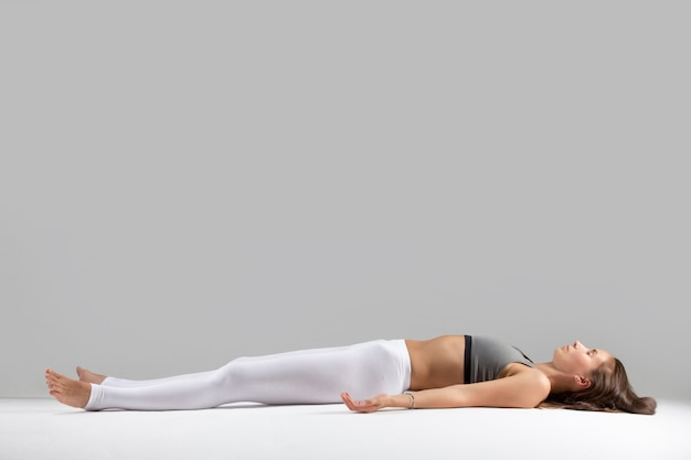 Young woman in Savasana pose, grey studio background Free Photo