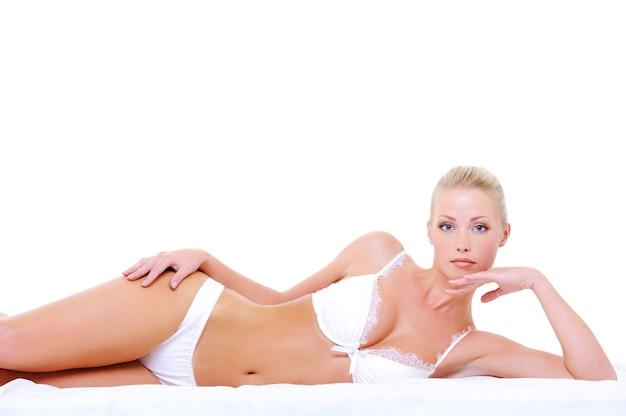 매혹적인 포즈에 누워 섹시한 흰색 란제리에 젊은 여자 무료 사진
