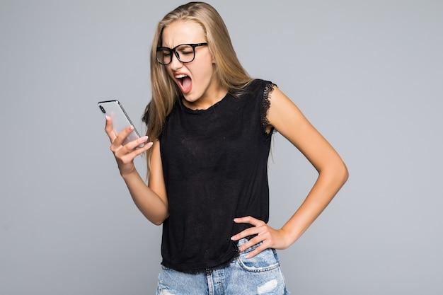 電話で叫んでいるシャツの若い女性孤立した灰色の背景 無料写真
