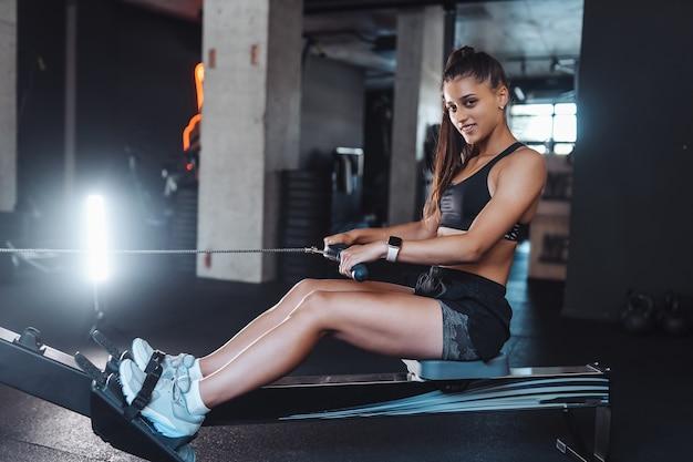 Молодая женщина в спортивной одежде в тренажерном зале, тренируясь и потягивая веса в сидячем кабельном тренажере. Бесплатные Фотографии