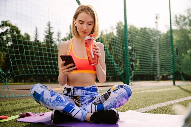 スポーツウェアの若い女性はマットの上に座って、水を飲み、スマートフォンを使用しています。 Premium写真