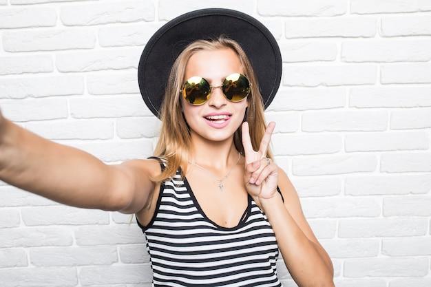 麦わら帽子とサングラスの白いレンガのオフィスの壁を越えて平和のジェスチャーでselfieスマートフォンを取る若い女性 無料写真