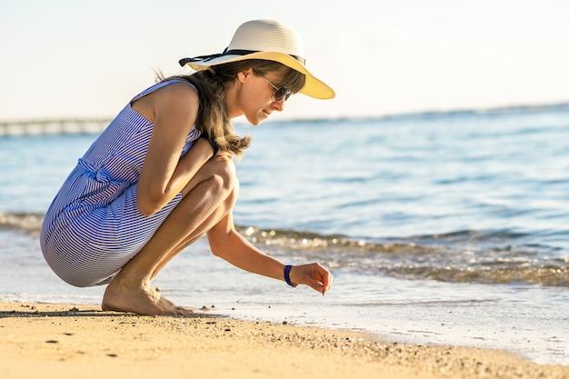 海のビーチの砂の上に何かを書いて夏服の若い女性。 Premium写真