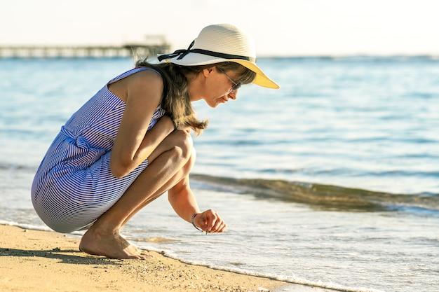 海のビーチの砂の上に何かを書く夏服の若い女性 Premium写真