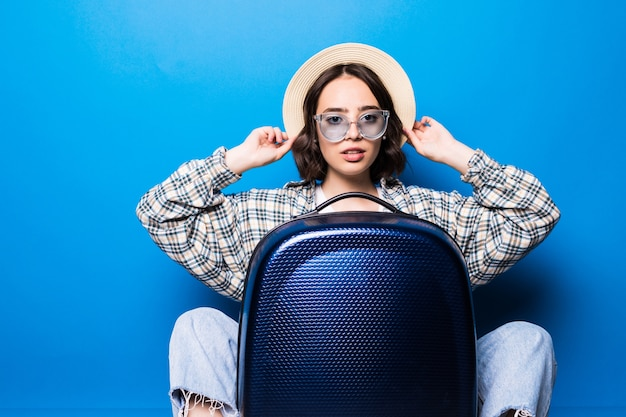 Молодая женщина в солнцезащитных очках и соломенной шляпе, сидя возле чемодана перед полетом. Бесплатные Фотографии