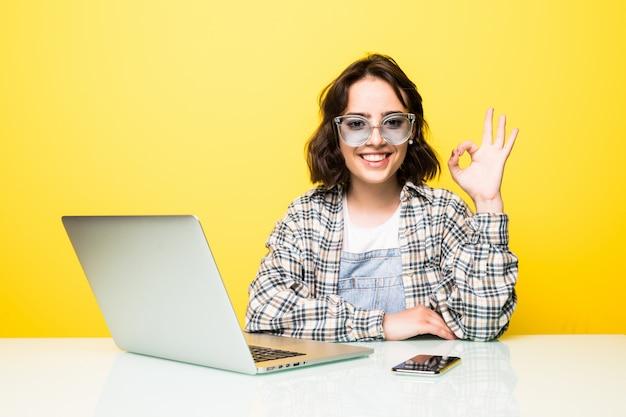 Молодая женщина в солнцезащитных очках, показывая знак ок, изолированные Бесплатные Фотографии