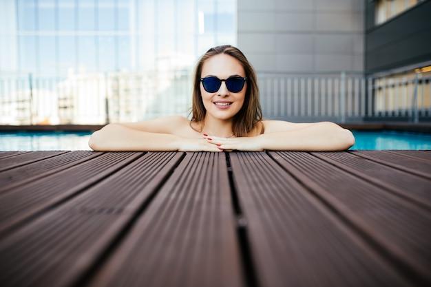 Молодая женщина в солнечных очках с идеальной белой улыбкой купается в бассейне на отдыхе Бесплатные Фотографии