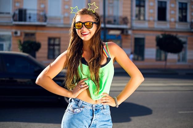 彼女の頭に緑のtシャツ、ジーンズ、サングラス、ネオン星を身に着けている通りの若い女性 無料写真