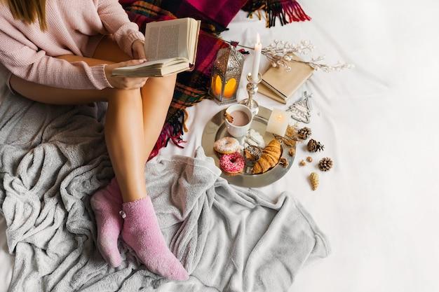 Молодая женщина в теплой шерстяной одежде сидит на кровати в ярком солнечном доме Бесплатные Фотографии