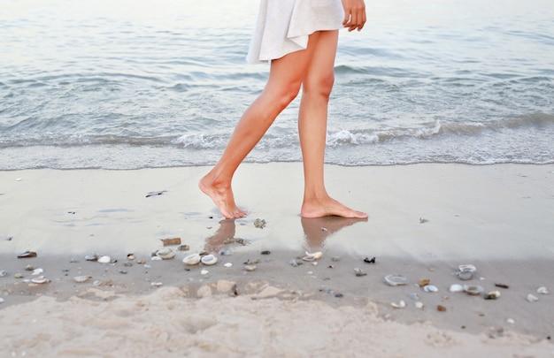 Молодая женщина в белом платье, ходить только на пляже Premium Фотографии