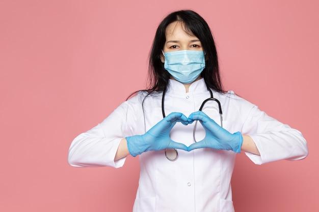 Молодая женщина в белом медицинском костюме синие перчатки голубая защитная маска со стетоскопом на розовом Бесплатные Фотографии