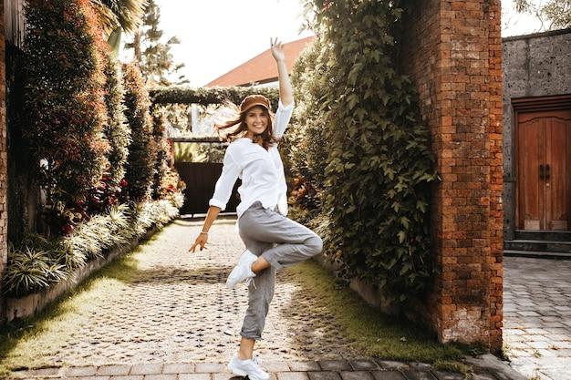 흰색 운동화, 회색 바지 및 대형 블라우스를 입은 젊은 여성이 담쟁이로 덮인 벽돌 울타리 공간에 대해 행복하게 점프합니다. 무료 사진