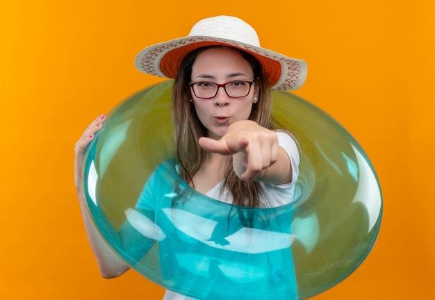 白いtシャツと夏の帽子の若い女性が正面を向いて膨脹可能なリングを保持しています。 無料写真