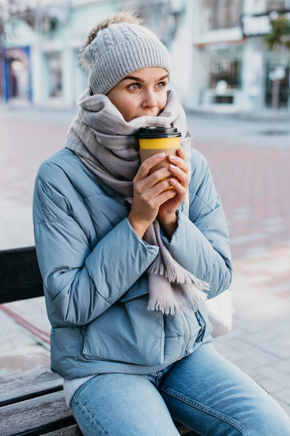 一杯のコーヒーを保持している冬の服を着た若い女性 無料写真