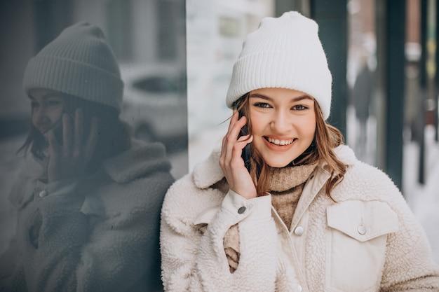 Молодая женщина в зимнее время по телефону за пределами улицы Бесплатные Фотографии