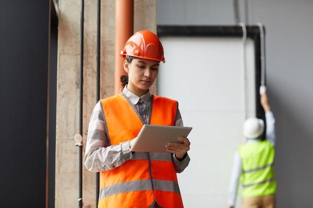 건설 현장에서 작업하는 동안 작업 헬멧과 디지털 태블릿을 사용하는 반사 조끼에 젊은 여자 프리미엄 사진