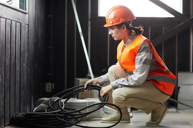그녀는 건설 현장에서 일하는 전선을 복용 작업 헬멧에 젊은 여자 프리미엄 사진