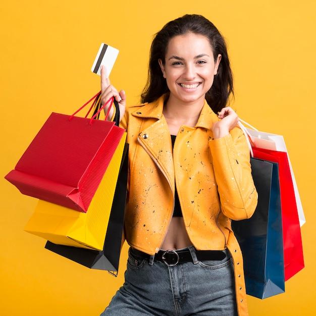 カードを保持している黄色の革のジャケットの若い女性 無料写真