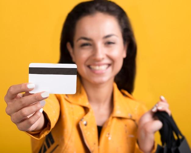 ショッピングカードを示す黄色の革のジャケットの若い女性 無料写真