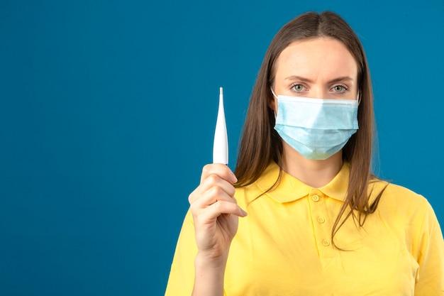 黄色のポロシャツと分離の青い背景に深刻な顔でカメラを見て手に温度計を保持している医療用防護マスクの若い女性 無料写真