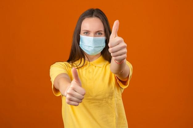 Молодая женщина в желтой рубашке поло и медицинской защитной маске, показывая большой палец вверх знак, глядя на камеру с позитивным выражением на оранжевом фоне Бесплатные Фотографии