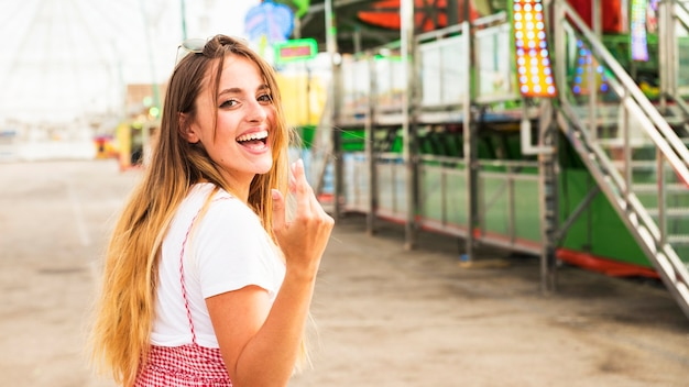 Young woman inviting someone to come at amusement park Free Photo