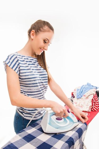 服にアイロンをかける若い女性 Premium写真