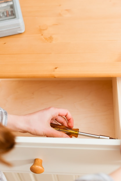 Young woman is assembling a cupboard Premium Photo