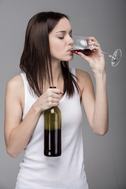 Young woman is drinking wine, isolated Premium Photo