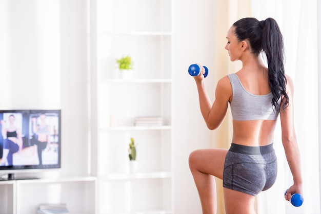 Young woman is exercising with dumbbells at home. Premium Photo